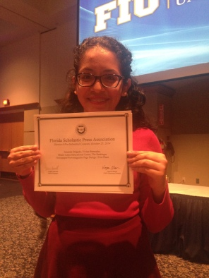 Vivian Bermudez holding up the certificate she and Amanda Delgado won for their newspaper layout.